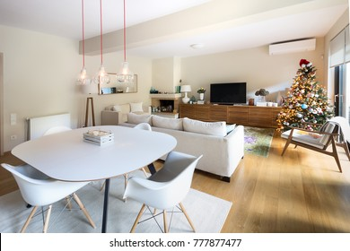 A large living  - dining room with a table, four white eiffel armchairs, a mid century style wooden arm chair, three edison lamps, a three seater sofa and a christmas tree, all on a wooden o