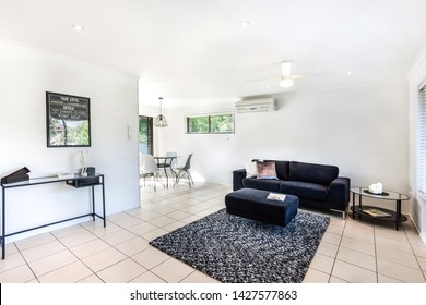 A large living room area featuring a contemporary style footrest lounge sofa, a showpiece table, AC