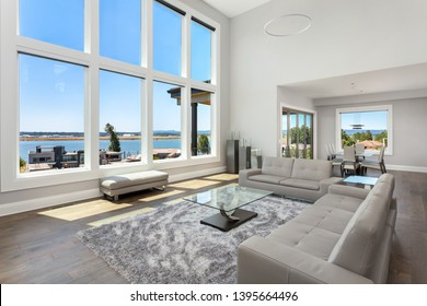 Large living room in new contemporary style luxury home with bank of windows showing gorgeous exterior view.