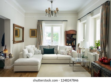 Large living room very bight  with oak wooden floor, four seats sofa, white carpet and retro objets, Greece.