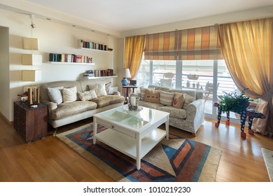 A large living room warm contemporary style with two sofas of two seaters, lamps, coffee table, carpet and stands on the wall with books. The floor is oak wood.