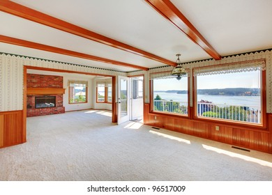 Large Living Room With Water View And Wood Beams And Beige Carpet.