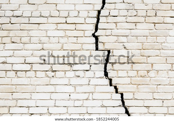 a large long crack in a white brick wall