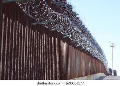 large loops of sharp razor wire hang on bollard style border wall at the US-Mexico border 5050