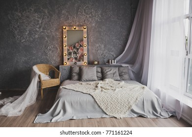 A large low bed in a room with huge Windows.