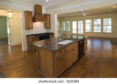 large luxurious kitchen with maple cabinets and black appliances