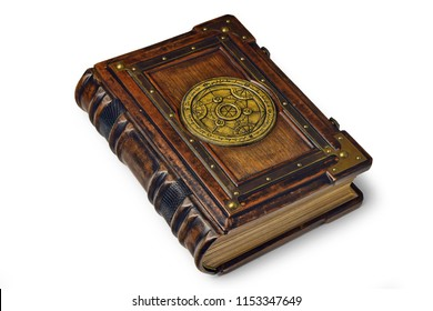 Large luxury leather - wooden book with a gilded transmutation circle in center of the front cover, attributed to a German alchemist from the 17th century. It laying on the table, angled on the left.