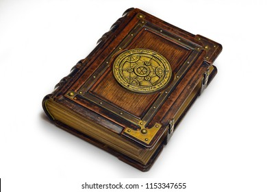 Large luxury leather - wooden book with a gilded transmutation circle in center of the front cover, attributed to a German alchemist from the 17th century. It laying on the table, angled on the right