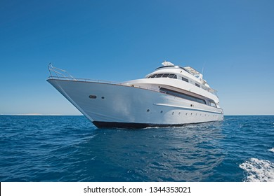 Large luxury motor yacht sailing out on tropical sea ocean with blue sky background