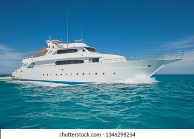 Large luxury motor yacht under way sailing out on tropical sea ocean with blue sky background