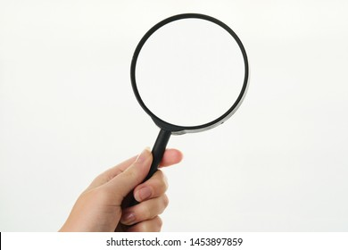 large magnifier in the hands of a girl on a white background