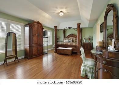 Large master bedroom with wood framed bed