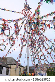 A large May Pole in a town. Decorated with ribbon the pole is raised on May day, in paganism called Beltane. People will dance round the pole holding a ribbon each and platting them. A Pagan ritual.