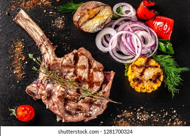 Large meat steak on the bone, grilled, served with grilled vegetables, corn, red onion, sweet peppers, potatoes. Modern serving dishes in the restaurant on a black slate blackboard.