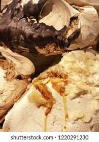 Large meringue with flakes, caramel sauce and fudge pieces with chocolate meringue in the background. Delicious background with space for text.
