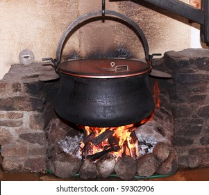 Large metal cauldron over a fire in a farm house used for boiling milk to make cheese in Switzerland.