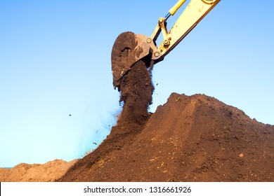 A large metal excavator bucket digs the ground. Parts of construction earthmoving equipment close-up. Digging and filling the soil with an excavator bucket.