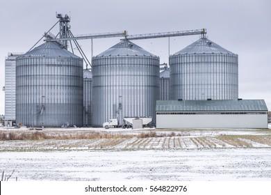 Large metal grain elevators dwarf a semi-trailer truck making a delivery.