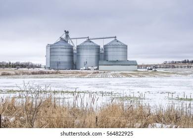 Large metal industrial silos dominates the landscape in rural Ontario Canada.