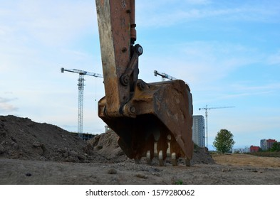 Large metal iron ladle. Excavator bucket for digging a pit for pouring concrete for the construction of a multi-story residential building at a construction site