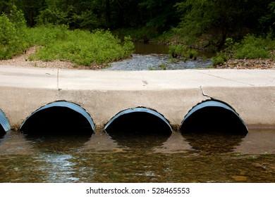 Large metal pipes under a concrete bridge