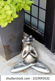 Large metal planter with bright green leaves hanging over the side and zen-like frog statue in yoga position, meditating.