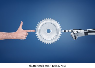 A large metal spur gear with a human and a robotic hand touching it from different sides. Robotics in manufacturing. Replacement for human labor. Technologies and electronics.