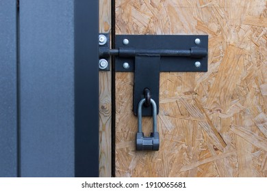 Large metallic padlock hanging on closed old fashioned door.