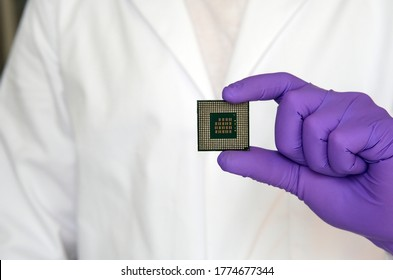 Large microchip (microprocessor) demonstrated by scientist in gloves and a white lab coat. Copy space.