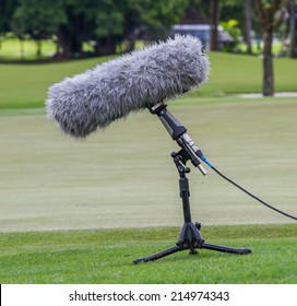 A large microphone boom with stand for TV or Radio situated at the grass.