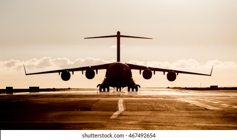 Large military cargo plane silhouette on an empty airstrip