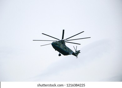 large military helicopter hovers in  sky. A camouflaged helicopter flies at high speed.