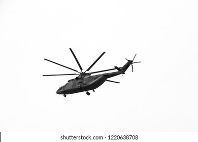 large military helicopter hovers in  sky. A camouflaged helicopter flies at high speed. black and white.