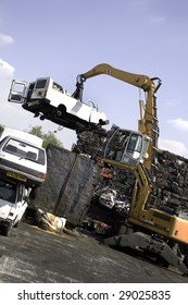 A large minibus being lifted by grab crane to be scrapped with other cars and scrapped cars around