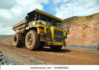 A large mining dump truck transports ore in a quarry