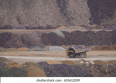 Large mining truck carrying ore across an open pit mine