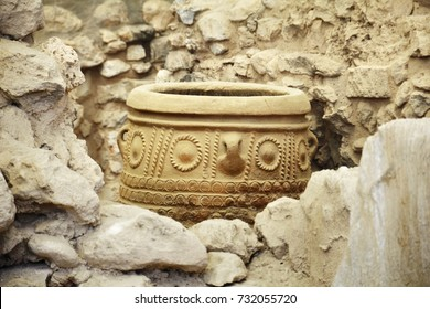 Large minoan vessel pithos decorated with geometric ornament at the background of ancient stone wall, magazine for food and wine in Knossos royal Palace near Heraklion, Crete island, Greece.