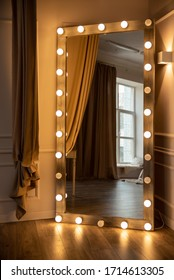A large mirror with lighting against the wall in the room. Yellow light lamps around the perimeter of the frame. Convenient mirror for applying makeup.