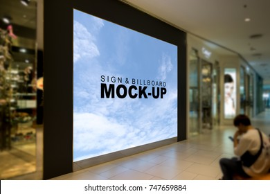 A large mock up blank billboard for advertising in front of the store inside the mall with young man sitting on the sidewalk and used mobile phone, copy space for text or graphic,  with clipping path