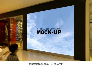 A large mock up sign billboard in front of the shop inside the mall with young man sitting on the sidewalk and look that, with clipping path
