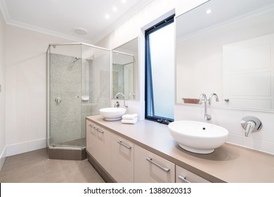 Large modern bathroom interior with his and hers vanities and glass shower.