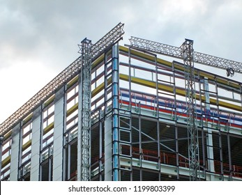 a large modern building site with construction scaffolding and steel girder framework with safety fences