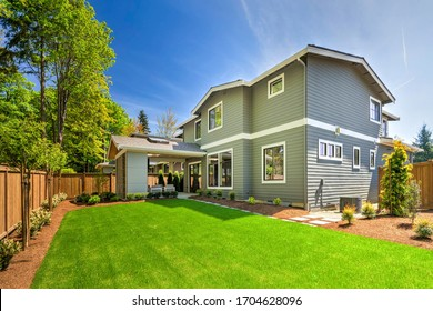 Large modern grey new house with back porch from back yard with green grass and nice landscaping.