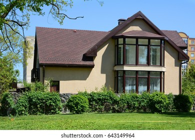 Large modern house with asphalt roofing shingles and lawn