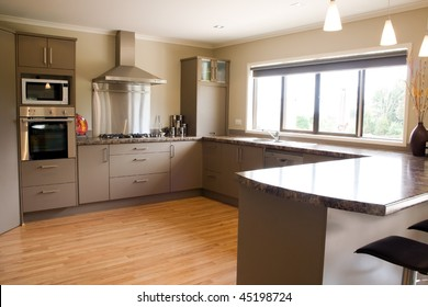 A large modern kitchen with stainless steel accessories and wooden floor