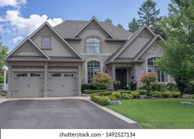 A large modern multi level residential executive home with brown and grey brick stone exterior, shingled roof, beautiful wooden garage doors, paved driveway, green gardens and lawn.