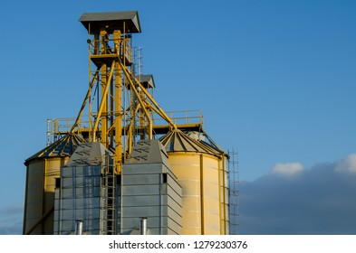 A large modern plant for the storage and processing of grain crops. view of the granary on a sunny day. Large iron barrels of grain against the sky. End of harvest season.