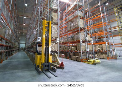 Large modern warehouse with metal pallet racks and forklift trucks
