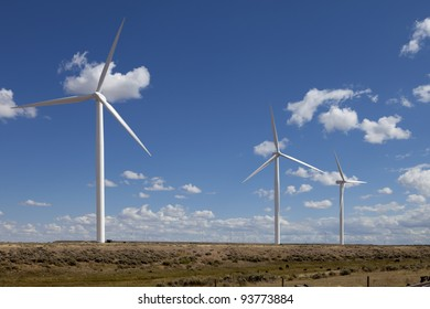 Large modern windmill (wind turbine) with blue sky in desert.