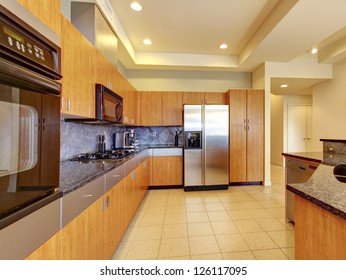 Large modern wood kitchen with living room and high ceiling and ivory walls.